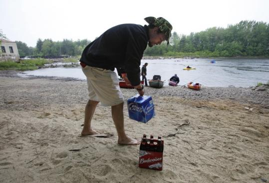 Daniel Overlook grabbed some beer as he headed out on the Saco River Sunday in Maine. Police are trying to limit rowdy behavior on the river.