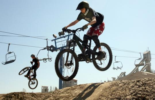 With ski jump towers as a backdrop, mountain bikers hit some of the 16 miles of trails at Canada Olympic Park.