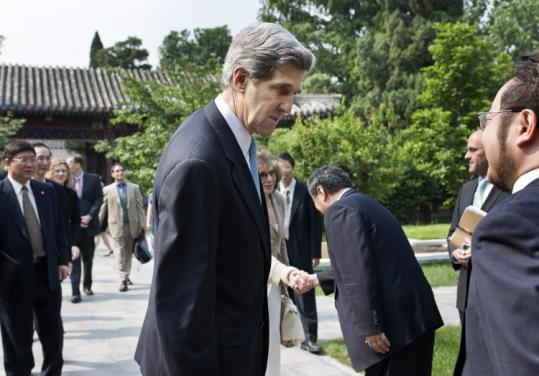 Senator John F. Kerry and his wife, Teresa Heinz (back), were greeted by Chinese officials earlier in the week in Beijing.