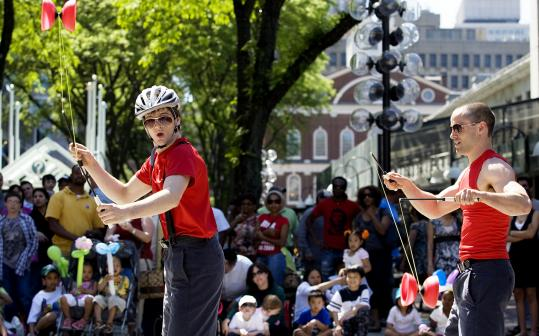 Jacob Sharpe (left) and brother Nate passed the diabolo during a performance at Faneuil Hall Marketplace.