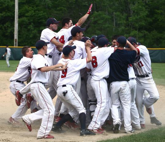 Lincoln-Sudbury players pile on Eric Watkins after his single in the ninth inning drove in the winning run.
