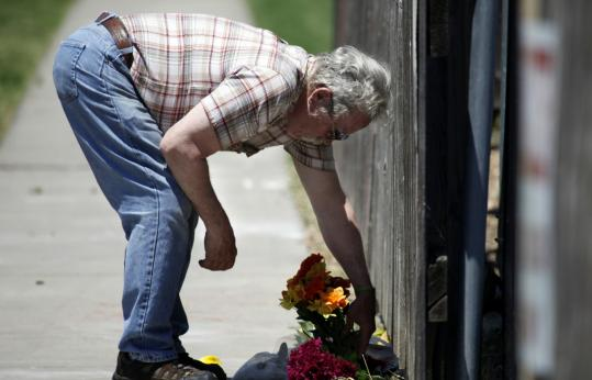 Thomas Dyke placed flowers at the gated entrance of Women's Health Care Services yesterday following the shooting death of Dr. George Tiller at a Wichita, Kan., church. Police arrested a 51-year-old suspect in the shooting.