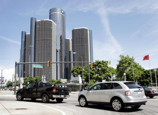 Cars drove past the General Motors headquarters in Detroit yesterday on the eve of the company's bankruptcy filing.