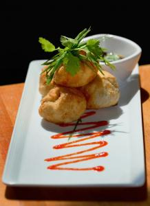 The momos at Tremont 647 are fried pork dumplings served with soy sauce and sriracha.
