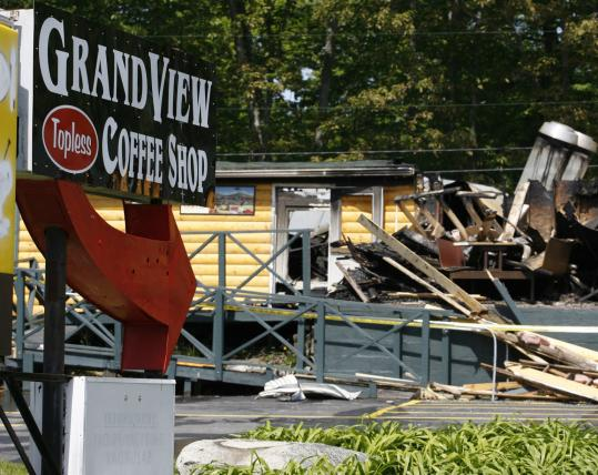 Five adults and two children who had been sleeping in rooms adjacent to the Grand View Coffee Shop when it caught fire escaped uninjured. Topless waitresses serve coffee and doughnuts at the shop.