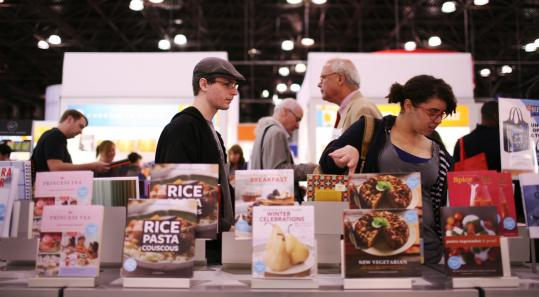 Visitors pass new titles at the Chonicle Books booth at last weekend's Book Expo in Manhattan.