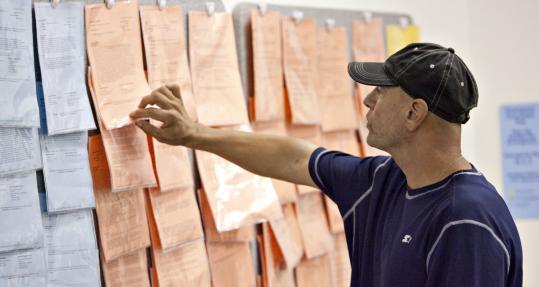Anthony Solis looked over job postings inside the Riverside Workforce Development Center in Riverside, Calif., this week.