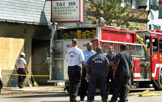 Firefighters talked among themselves at the scene of a fatal fire on Centre Street, in which two Boston firefighters were killed.