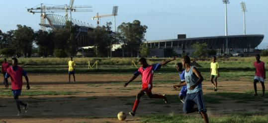 South African youths play soccer in the shadow of Royal Bafokeng Stadium in Rustenburg, one of four venues for the upcoming Confederations Cup. The country hosts the World Cup in 2010.