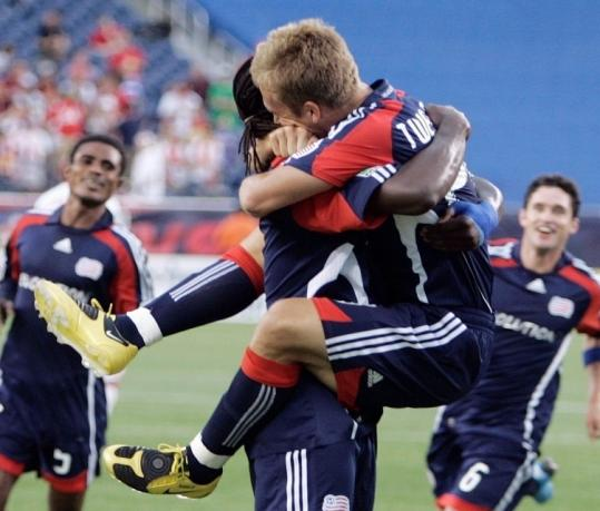 Taylor Twellman (right) gets a celebratory lift and hug from Shalrie Joseph after Twellman scored his 100th goal.