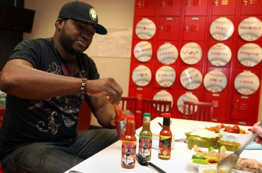 JONATHAN WIGGS/GLOBE STAFFSox slugger David Ortiz checks out the four different hot sauces sold under the Big Papi name. The hotness level runs from mild (Original En Fuego) to fiery (Grand Slam En Fuego).