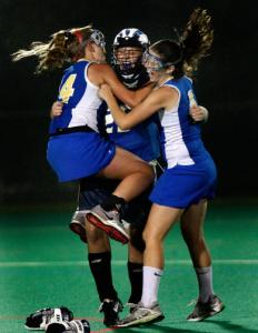 Norwell's Laura Ferzoco (left) and Leah Smith celebrate with goalie Justine Sullivan.