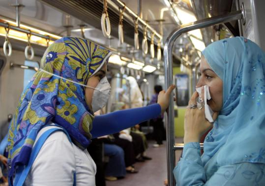 An Egyptian woman wore a surgical mask as another covered her nose in Cairo's underground yesterday.