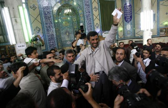 President Mahmoud Ahmadinejad (left) greeted his supporters before casting his ballot in Iran's hotly contested presidential elections yesterday in Tehran. Leading challenger Mir Hossein Mousavi, his finger inked, flashed a victory sign after casting his vote on the outskirts of Tehran.