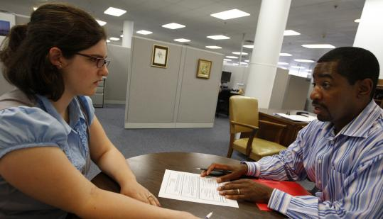 Edgar Howe, the Youth-Links program director at the South Coastal Career Center in Quincy, assists Kristen Bardon with an application for summer employment.