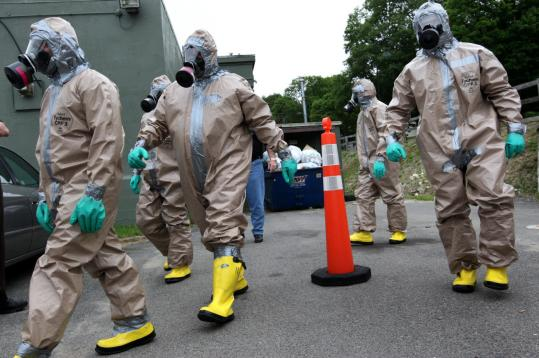 Emergency responders practiced for disaster in protective suits at the DelValle Institute in Mattapan.