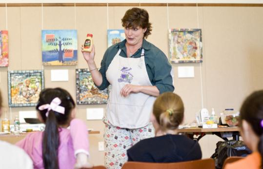 Katie Wilton talks about ingredients before her cooking class of tweens at the Brookline Public Library start making things like strawberries with cream cheese, topped by a blueberry.
