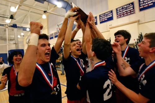 The Lincoln-Sudbury boys' volleyball team celebrate with the title trophy.