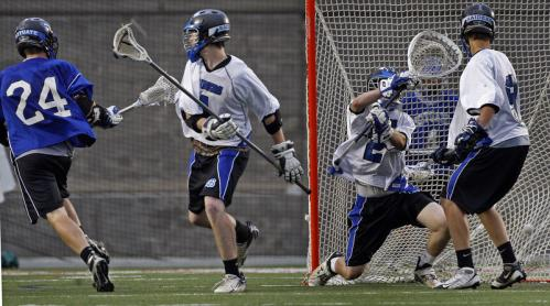 Scituate's Kyle Crowley (24) fires the ball past Dover-Sherborn goalie Jeff Wiliams as he scores in overtime to give his team a 7-6 victory.