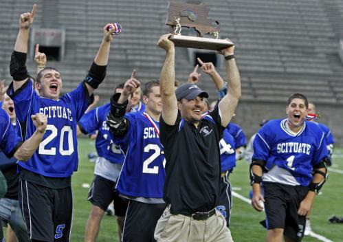 Scituate head coach Mark Puzzangara holds the Division 3 championship trophy after his team defeated Dover-Sherborn, 7-6, in overtime at Harvard Stadium. Stroll through our gallery to see scenes from that game, as well as the Division 1 championship tilt between Duxbury and St. John's Prep.
