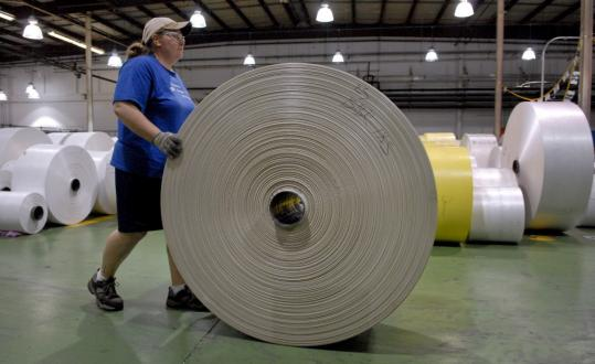 A machine operator moved a roll of plastic film to be turned into plastic bags at Hilex Poly Co. in Pennsylvania. Some economic indicators suggest the manufacturing slump may be easing.