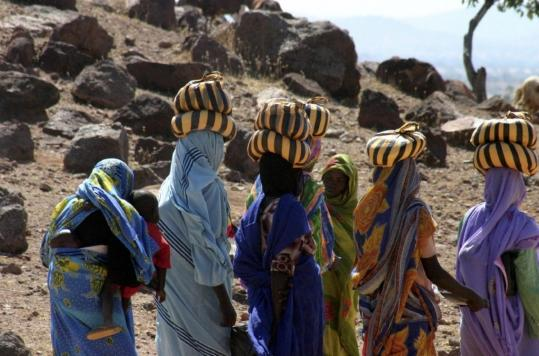 In this image provided by Physicians for Human Rights, Darfuri women return to a UN refugee camp near Farchana, Chad.