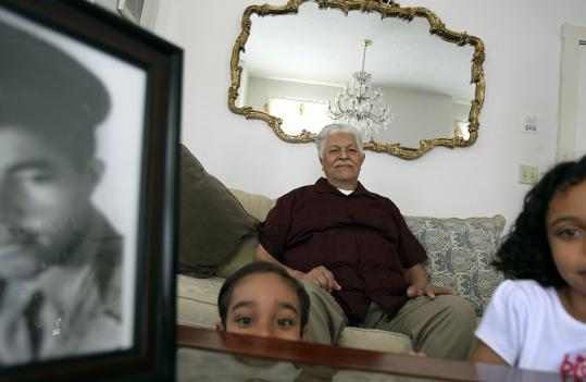 The Rev. Jose Perez sat at home in Worcester with his grandchildren Elias and Daviana. He served in the Army's 65th Infantry Regiment.