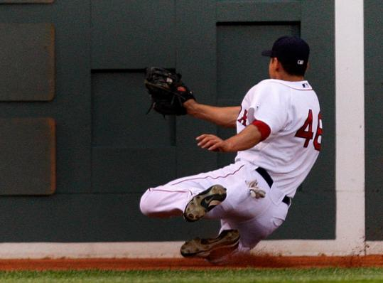 Jacoby Ellsbury managed to flag down Jeff Francouer's liner and slow his momentum before sliding into the base of the Monster.