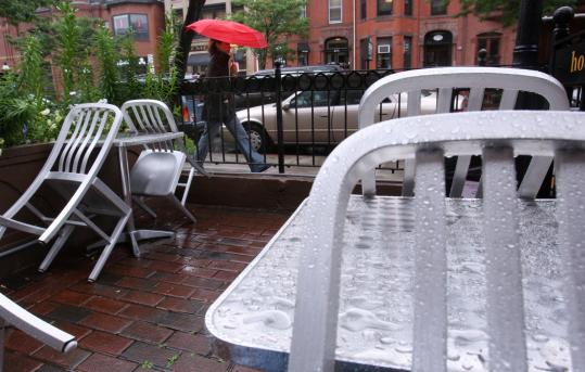 Raindrops took all the good seats yesterday outside a Newbury Street restaurant. Wet weather has hurt business citywide.