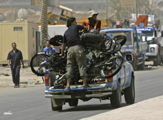 Iraqis removed destroyed motorcycles yesterday in Baghdad after a bomb exploded in a crowded market.