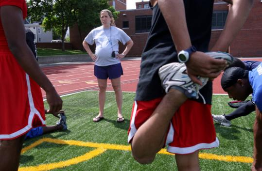 Charlestown High School track coach Kristyn Hughes worked with her team during practice at the school's track.