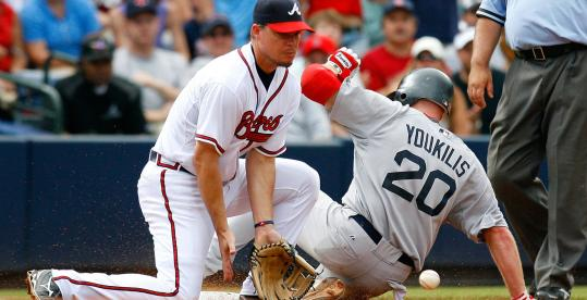 Kevin Youkilis slides past Chipper Jones for a two-out triple in the eighth; he was stranded, unable to add an insurance run.
