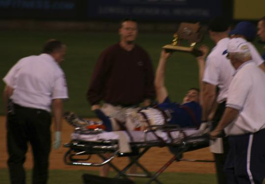 With unbroken spirit, Chris Halliday holds the championship trophy aloft as he is taken off the field strapped to a stretcher.