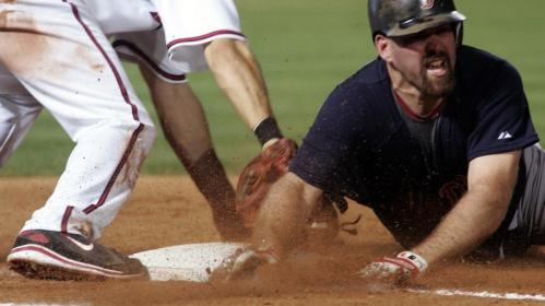 Kevin Youkiilis, right, is tagged out sliding back to first base by Atlanta Braves Casey Kotchman during the eighth inning.