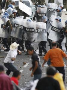 Supporters of Honduras's President Manuel Zelaya clash with police near the presidential residency yesterday.
