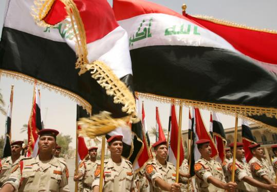 Iraqi soldiers (above) held up their national flag yesterday as they paraded on the grounds of the former Iraqi Defense Ministry, the last position occupied by the US military in Baghdad.