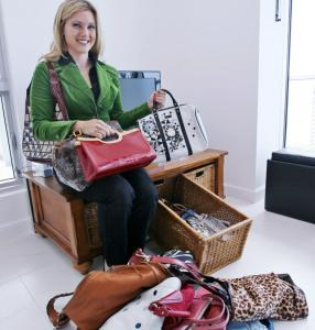 Cassandra Smith held four designer handbags that she rents. The pile on the floor are some she owns but doesn't use.