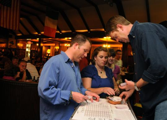 Trivia night scorekeeper Steve Grant (left) and host Joel Bates, both educators, tallied scores at the Old Timer in Clinton last week as Jennifer Frommer, a contestant, submitted a team response. Some 200 weekly trivia nights are held across New England.