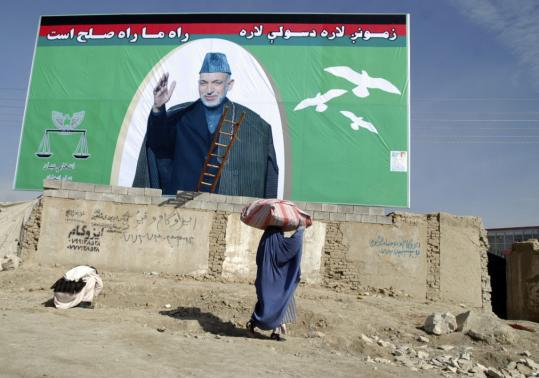 A woman walked under an election campaign banner of Afghanistan President Hamid Karzai, who has pardoned drug traffickers tied to well-respected families.