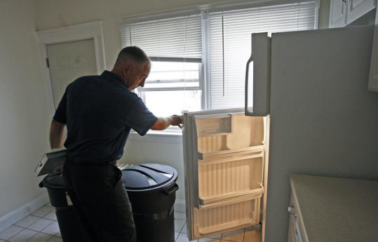John Ferrara inspects a rental unit. The Revere housing inspector is among the city workers whose pay and workweek have recently been cut due to budget constraints.
