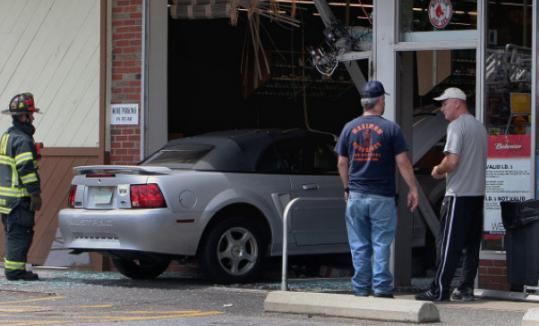 A car was left halfway through a storefront after a crash in Natick, injuring a clerk inside.