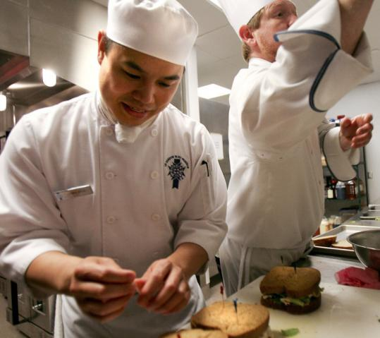 Erwin Chuk (left) works alongside chef instructor Russell Ferguson at Technique, Le Cordon Bleu's teaching restaurant.
