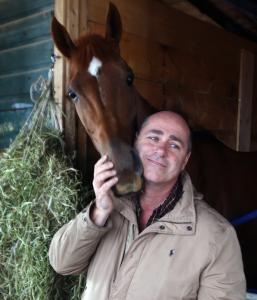 """I love the horses. It's my passion,'' says trainer/owner Giuseppe Iadisernia. Here he greets Gadamis at Suffolk Downs."