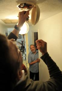 Bill Johnson, volunteer for a fix-it program in Sudbury, checks a smoke detector for Shekhar Mehta.