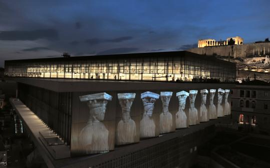 The caryatides are projected onto the wall of the New Acropolis Museum, which opened June 20 in the shadow of the Parthenon.