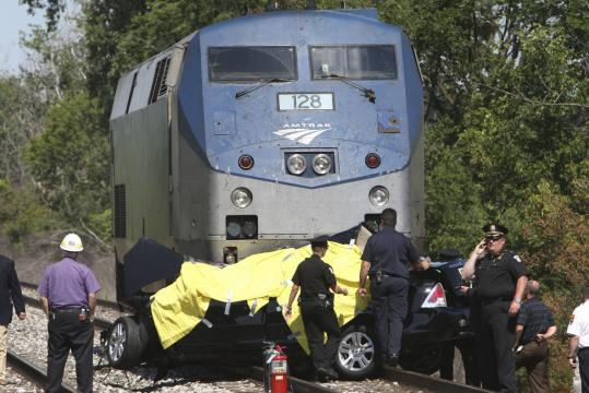 Police at the scene where a train struck a car near Detroit, killing all five people in the sedan. Police said the crossing has a gate and flashing lights that apparently were working when the car approached. The train's passengers were bused to another train.