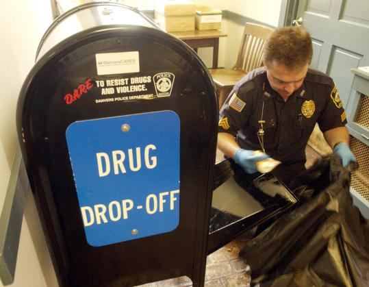 Police Sergeant Robert Bettencourt empties Danvers' prescription drug dropoff box.