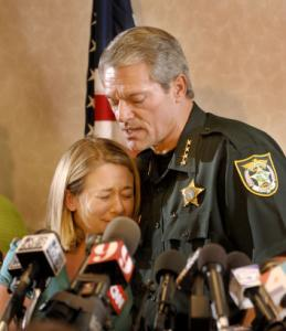 Ashley Markham was comforted by Sheriff David Morgan after he announced a seventh arrest in the shooting death of her mother.