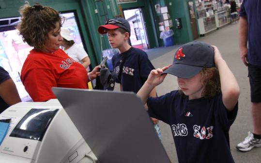 Danvers transplants living in Virginia, the Kelleys watch every Red Sox game. From left, Jacquie, Spencer, and Victoria looked at merchandise yesterday at Twins Souvenirs near Fenway Park.