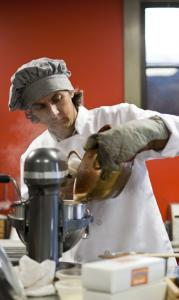 French-born confectioner Didier Murat, maker of Vadeboncoeur nougat, pours hot ingredients into a mixer.